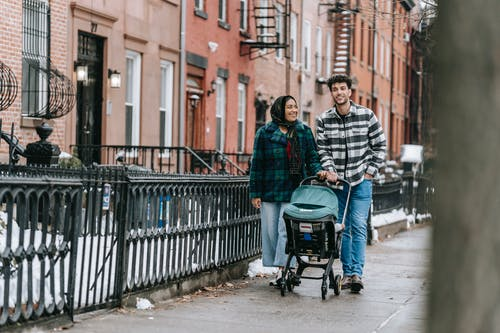 Full body of positive ethnic couple pushing stroller with baby while strolling along street in winter day