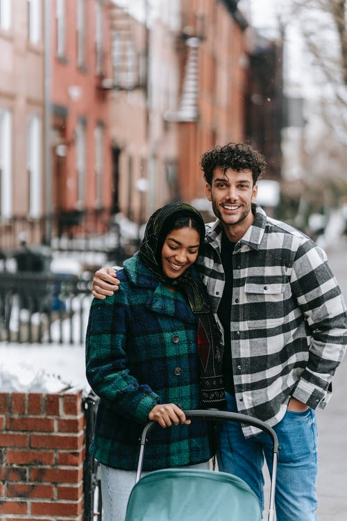 Smiling ethnic couple in casual clothes standing on sidewalk with stroller in winter day