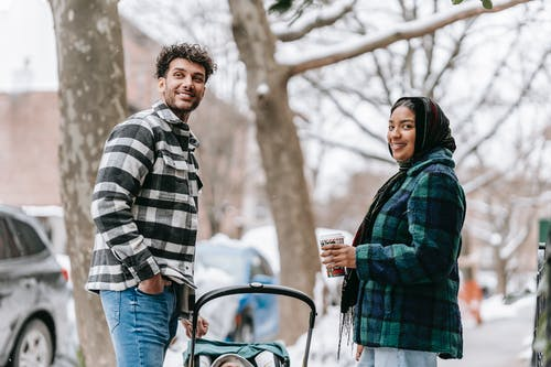 Smiling ethnic couple standing on roadside with baby in stroller