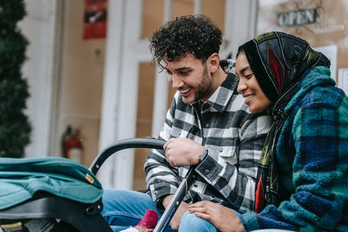 Cheerful young multiethnic spouses smiling and looking at baby in stroller