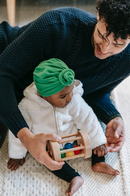 From above of crop happy ethnic man in casual clothes playing with cute black daughter in turban sitting on carpet at home