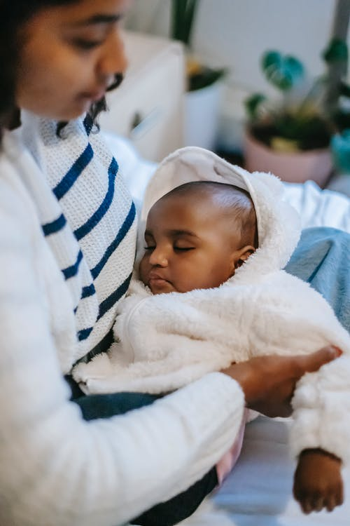 Side view of crop young African American female in casual clothes hugging cute little sleeping baby while sitting on sofa at home