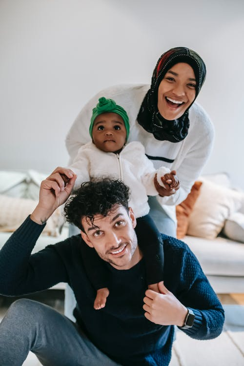 Cheerful young multiracial parent with curious baby smiling and looking at camera while having fun during weekend at home