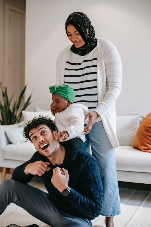 Happy young Muslim black woman standing near cute little daughter sitting on shoulders of cheerful ethnic father during weekend at home