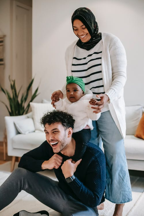 Positive young multiethnic couple in casual clothes laughing while playing with cute little daughter during weekend at home