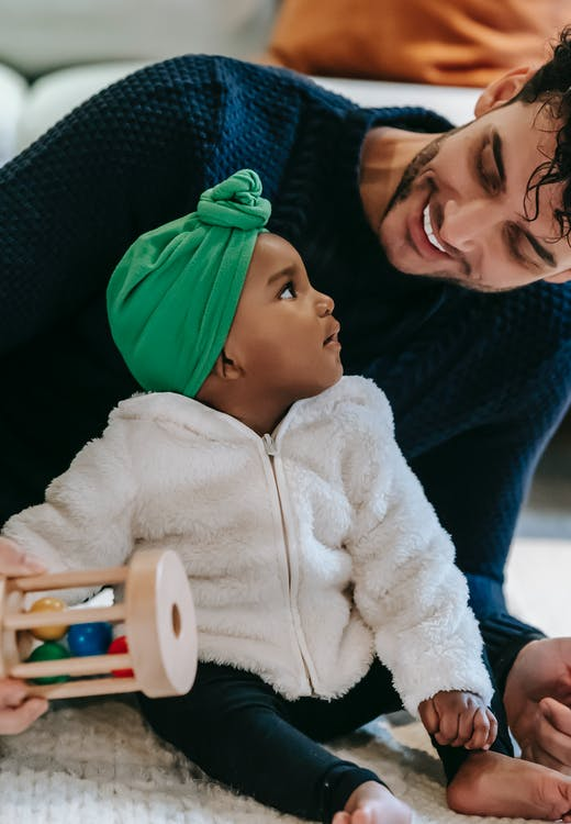 Smiling young ethnic man playing with curious baby on carpet at home