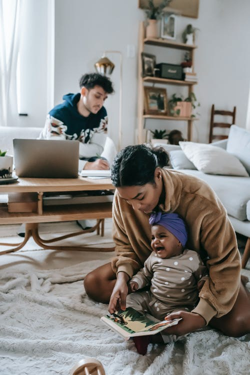 African American mother and black baby sitting on rug with book in living room near ethnic father at table with laptop