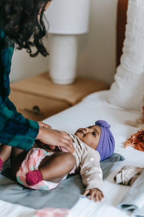 Crop black mother with baby on bed