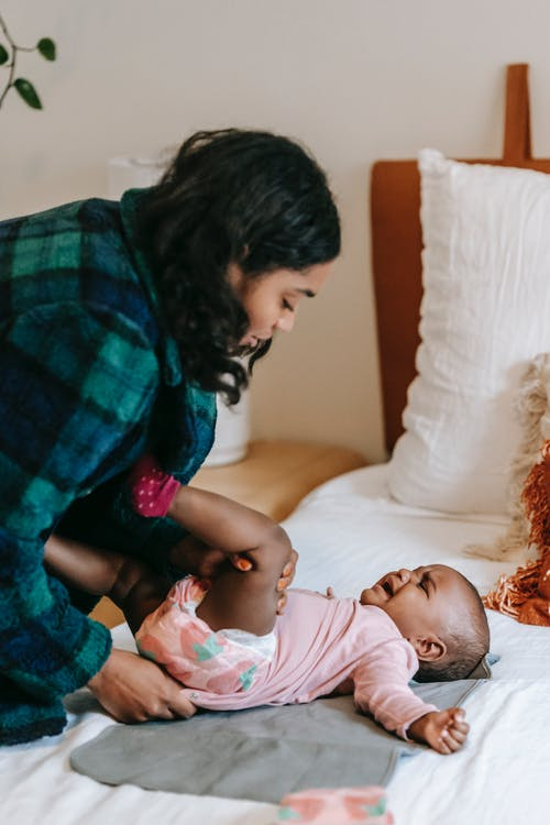 Side view of serious African American mother putting clothes on unhappy black baby lying on bed in bedroom at home