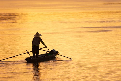 Anonymous man in boat on bright sea at sunset