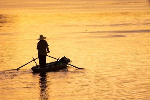 Back view of anonymous male silhouette in hat admiring bright rippled ocean from wooden boat with paddles in twilight