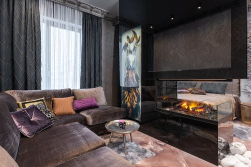Interior of modern cozy apartment with comfortable sofa placed near contemporary burning firewood in room with bed at stylish home