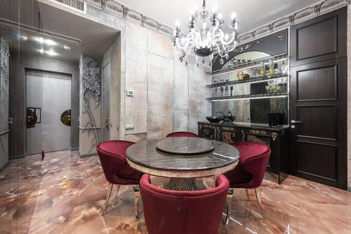 Interior of modern spacious kitchen with round table and red chairs placed near contemporary counter with kitchenware in stylish apartment