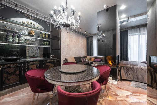 Armchairs at table placed near kitchen counter with kitchenware in modern spacious apartment with bed near burning fireplace and couch