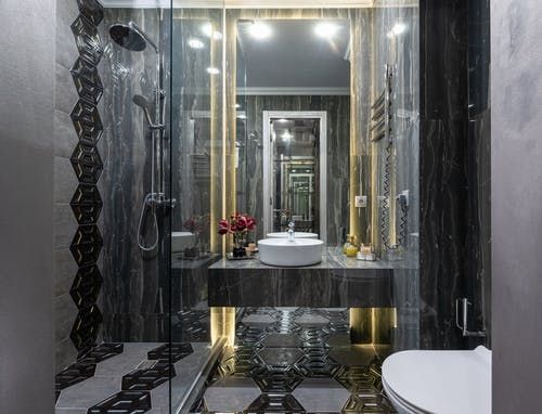 Interior of spacious contemporary bathroom with black tiled walls and floor with transparent shower cabin near bidet and sink at mirror