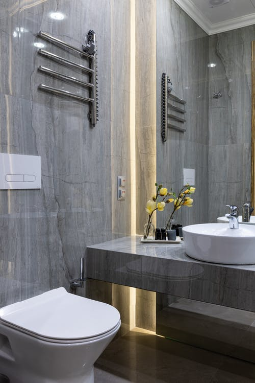 Interior of modern bathroom with sink placed at mirror on marble gray surface with flowers near white ceramic bidet at home