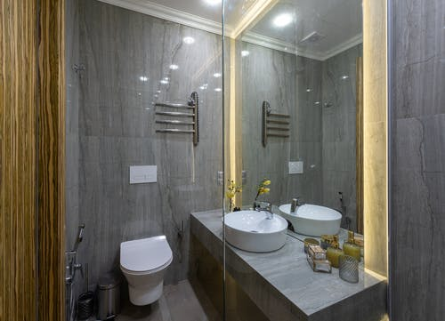 Interior of stylish restroom with gray walls and ceramic bidet near white sink reflecting in big mirror in light bathroom