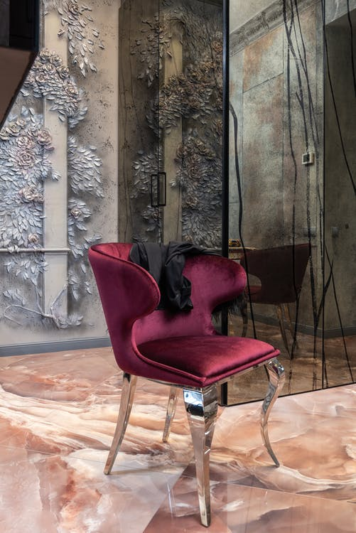 Comfortable red armchair with black textile placed on floor near wall with decorative elements in room with mirror at home