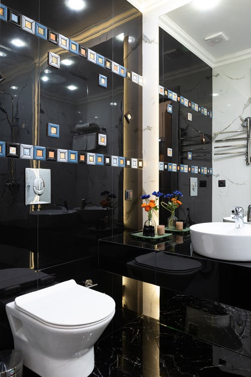 Interior of modern restroom with black tiled wall with sink placed on marble surface with flower near white bidet at home