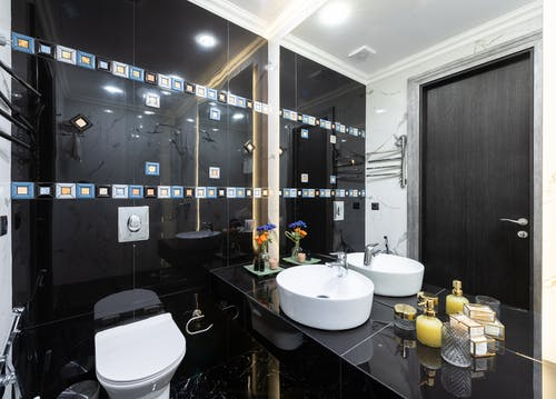 Interior of stylish restroom with white bidet installed at black tiled wall near flowers placed near sink at big mirror