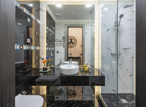 Interior of contemporary bathroom with bidet and black cupboard with sink and decorations placed near glass transparent shower cabin at home