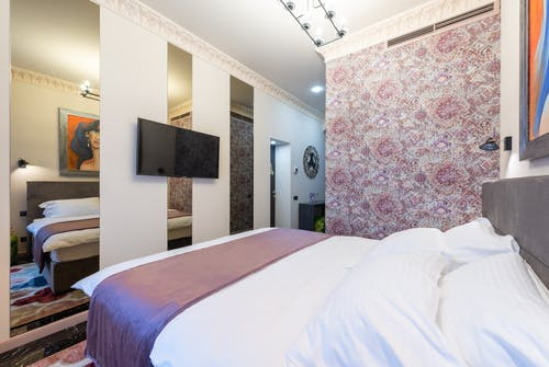 Stylish cozy light hotel suite with bed against TV hanging on wall with mirrors and wall with pink floral ornament