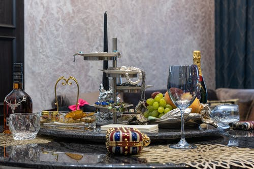Tray with jewelry and bijouterie with fresh grapes and fruits placed on table with wineglass and bottles of alcoholic drinks in room