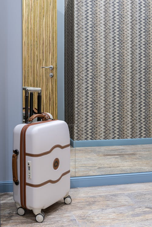 Modern baggage placed on floor near reflective mirror against wall with wooden door in corridor of hotel room during trip