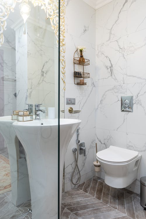 Interior of stylish restroom with white sink placed between glass transparent shower cabin and bidet at tiled wall at home