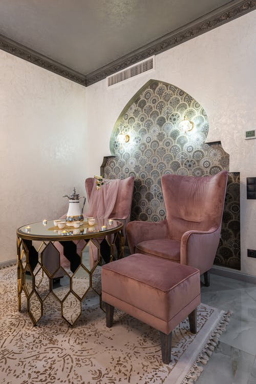 Glass table with teapot and set of cups with burning candles placed between soft pink armchairs and pouf near decorated wall
