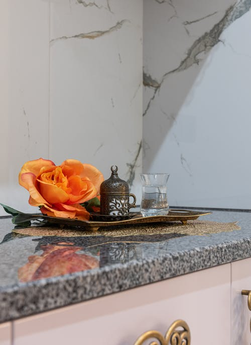 Traditional antique coffee cup and glass of water placed on marble surface of cupboard with orange rose near wall in room