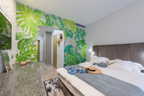 Comfortable bed with straw hat placed in hotel suite with decorations and green painted wall during trip in tropical country