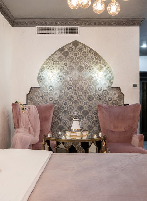 Stylish bedroom with comfortable bed and side table with set of cups and teapot placed between pink armchairs near ornamental wall