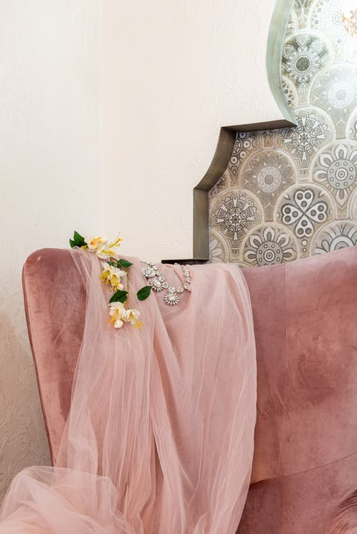 Silver necklace near artificial flower sprig on crumpled cloth on soft cushion in living room