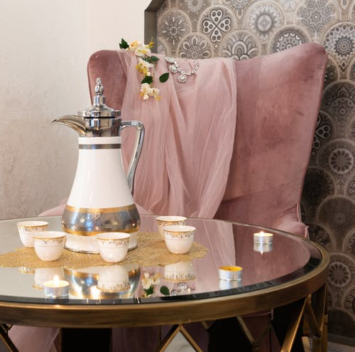 Oriental teapot and ceramic cups with ornament on table near burning candles against decorative cushion in living room