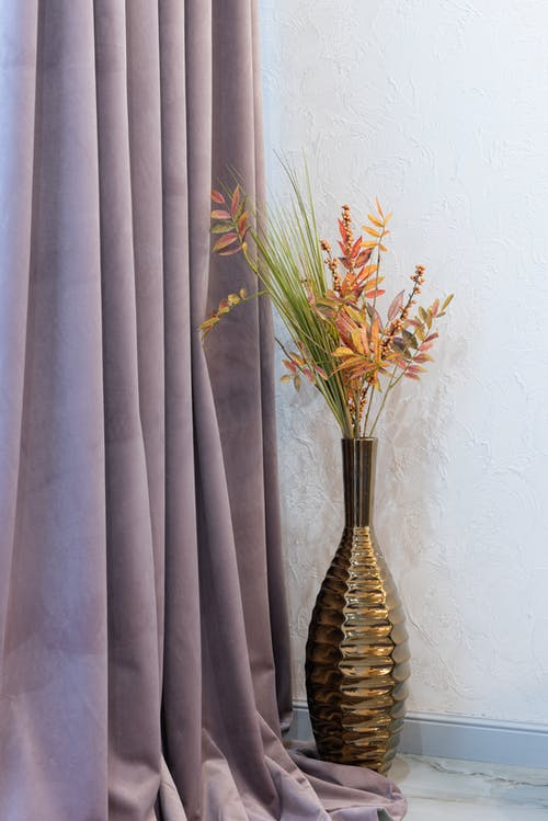 Assorted plant sprigs in decorative vase at home