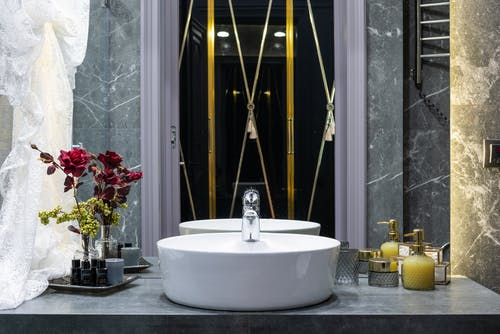 Washstand with tap between flower in vase and assorted hygiene products reflecting in mirror at home