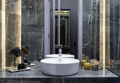 Contemporary bathroom with washstand between plant sprigs and hygiene products against mirror in house