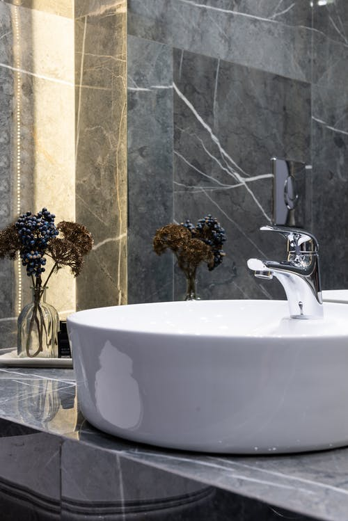 Washstand with shiny metal tap against plant sprigs in vase reflecting in mirror in modern bathroom