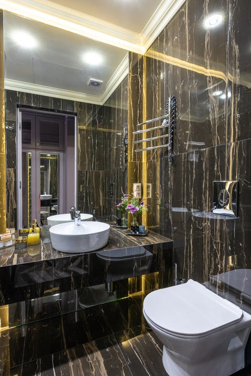 Contemporary bathroom with toilet bowl and washbasin reflecting in mirror under glowing lights in house