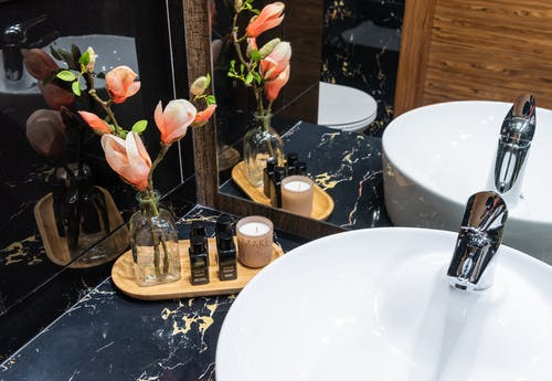 Decorative flowers in vase on tray with bottles and candle near washstand reflecting in mirror