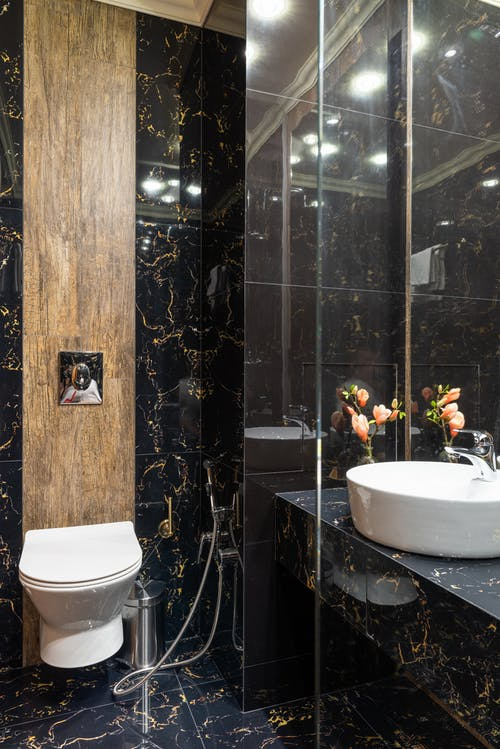 Modern bathroom interior with black marble walls and floor