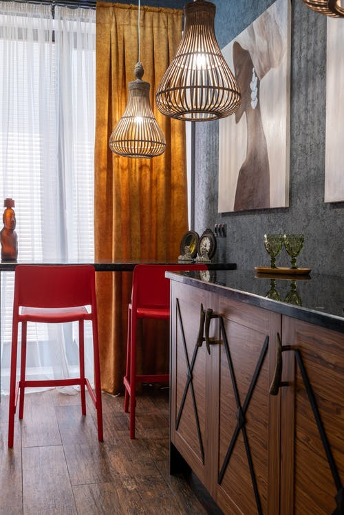 House with decorative glasses on cabinet against chairs and table on wooden floor under glowing lights