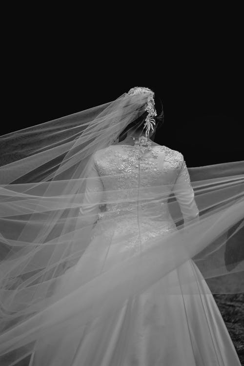 Unrecognizable bride in white dress with veil