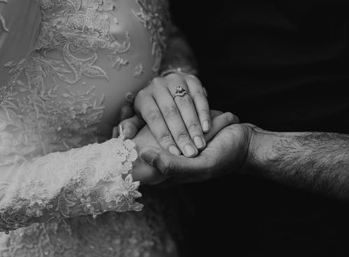 Black and white of romantic anonymous bride wearing white dress and engagement ring caressing unrecognizable loving groom during wedding celebration