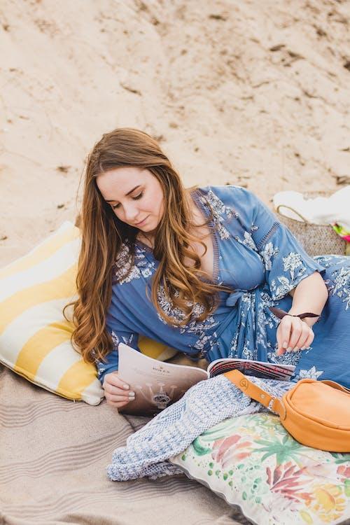 Focused woman reading magazine on beach