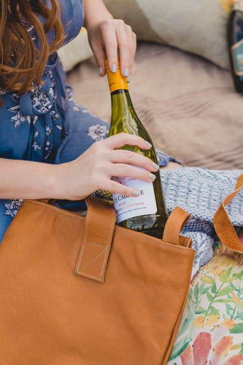 Crop woman opening bottle of wine during picnic