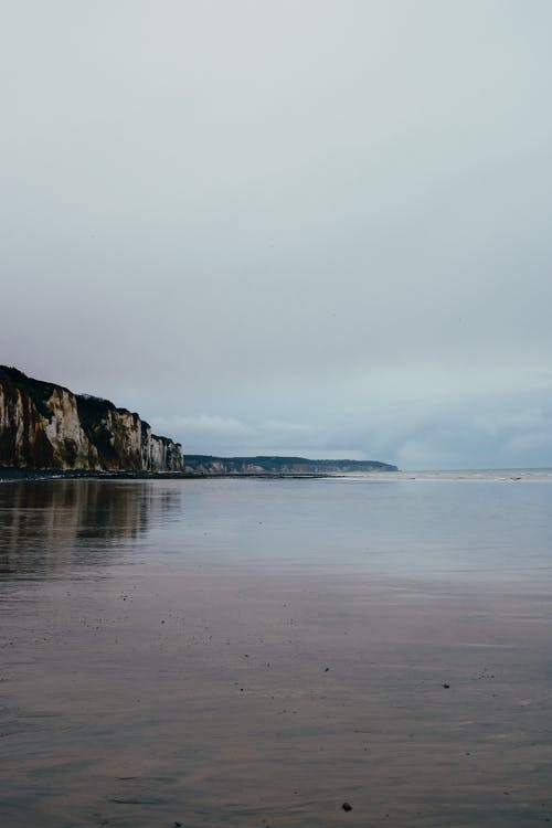 Picturesque view of vast rippling sea near rough stiff cliffs under gray cloudy sky