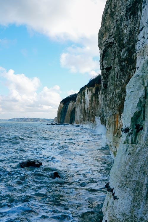 Scenic view of rough rocky cliff washed by foamy sea waves under clear blue sky