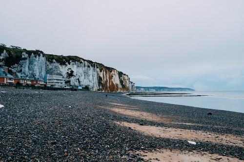 Rocky seashore with black beach near calm sea
